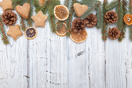 fur tree: Christmas decoration frame on old grunge white wooden board with fur tree branches, cookies, pine cones. Flat lay with copy space.