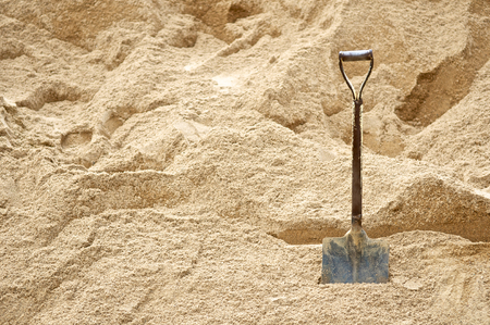shovel in dirt: Construction site with shovels on pile of dry soil and sand for background with text. Architecture project. Close up.