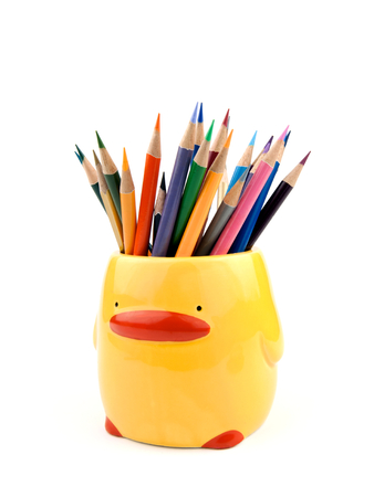 orange color: Many color pencils in cute cup or box isolated on the white background. In yellow duck shape mug or holder for kid. Material is ceramics. Close up.