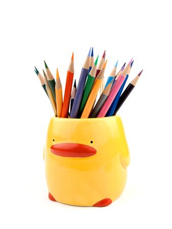 lapices: Muchos l�pices de colores en la taza o caja linda aislados en el fondo blanco. En amarillo taza forma de pato o el titular para el ni�o. El material es cer�mica. De cerca. Foto de archivo