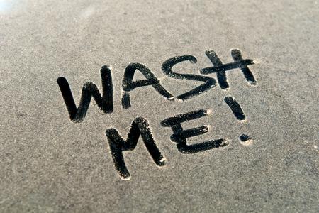 WASH ME !, Auto Staub Wort auf schmutzigen Heckscheibe des Autos und Inschrift WASH ME !. Front- und Seitenansicht. Close up von Text mit der Handschrift.