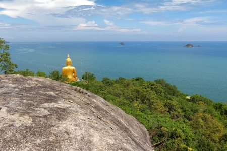 mountain view: back view of big golden Buddha statue on the mountain above the sea