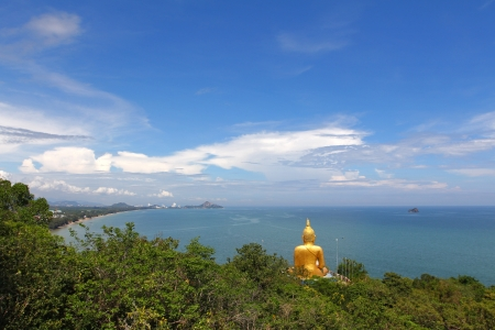 mountain view: back view of big golden Buddha statue on the mountain above sea