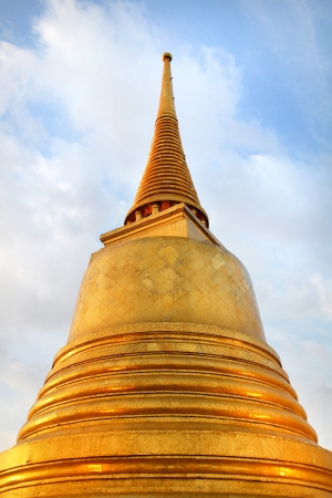 golden buddhist pagoda against blue sky with white clouds