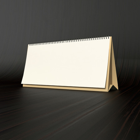 blank white table calendar on dark wood background photo