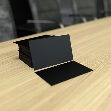 presentation card: a pile of blank black visit cards on wooden tabletop