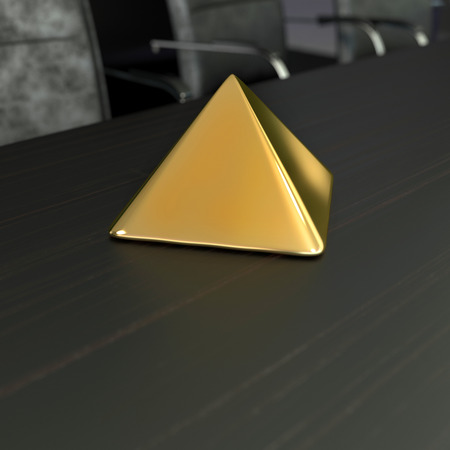 constancy: simple golden pyramide on the table in office room Stock Photo