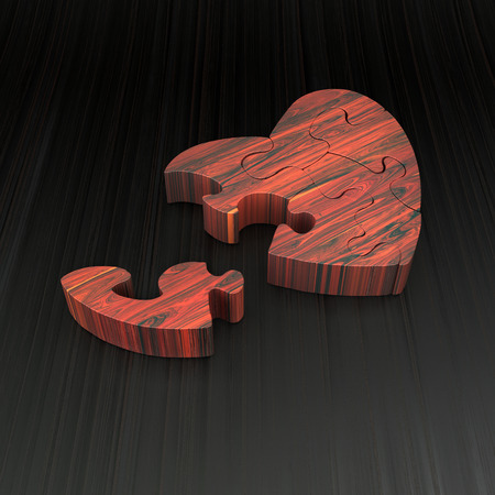 heart shape object made of red wood puzzle on dark surface photo