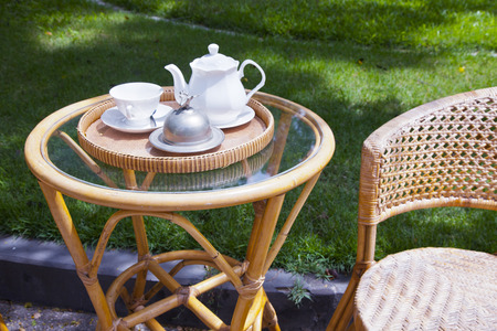 wicker furniture and white tea set in outdoor space photo