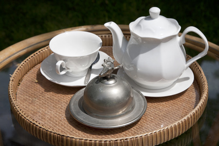 white teapot and tea cup on a small table in natural environment photo