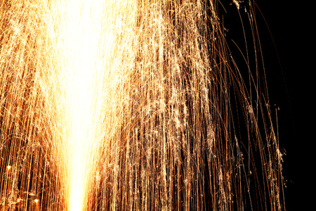 fire works: bright yellow festive fire works in night sky close up view