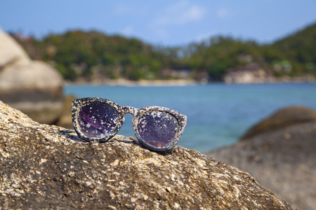 forlorn: plastic sunglasses after prolonged exposure to sun and sea, lying lonely on the stone