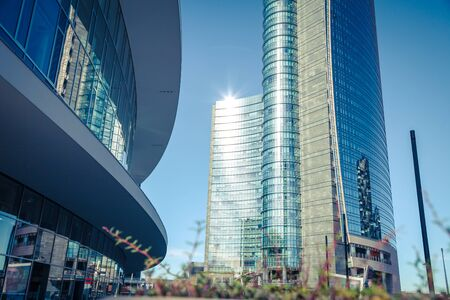 Architectural composition with modern city view, tall building with shiny glass facade and other object rounded architectural elements