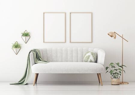 Poster mockup with two vertical frames on empty white wall in living room interior with gray velvet sofa, round pillow with tropical pattern, green plaid, lamp and plant in basket. 3D rendering. 스톡 콘텐츠