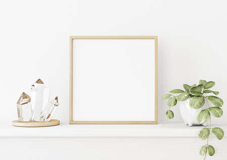 Interior poster mockup with square wooden frame on the shelf with green plant in pot, crystals and trendy decoration on empty white wall background. 3D rendering, illustration. Imagens