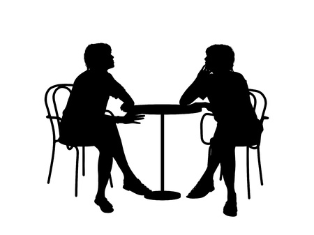 silhouettes of two young women sitting at the table in a cafe and talking to each other photo