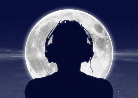 escuchando musica: silueta de un hombre en auriculares escuchando la música con la luna llena en el fondo Foto de archivo
