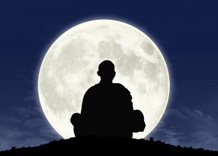 バック グラウンドの満月と瞑想の僧侶のシルエット