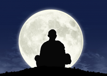 silhouette of a buddhist monk in meditation with the full moon on the background