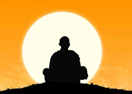 背景に太陽が昇ると瞑想の僧侶のシルエット