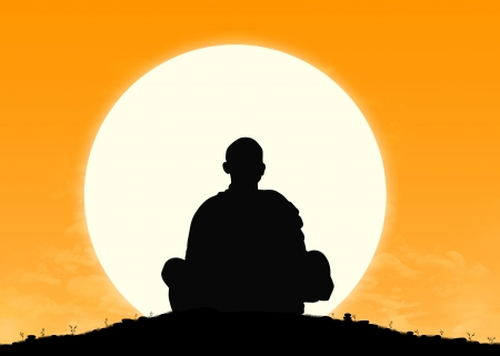 silhouette of a buddhist monk in meditation with the rising sun on the background Stock Photo