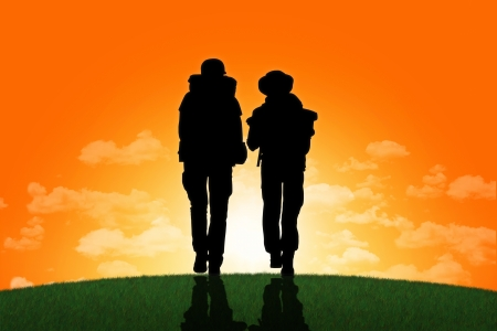 silhouettes of two backpackers, a man and a woman, walking together on a top of the hill towards the sunset