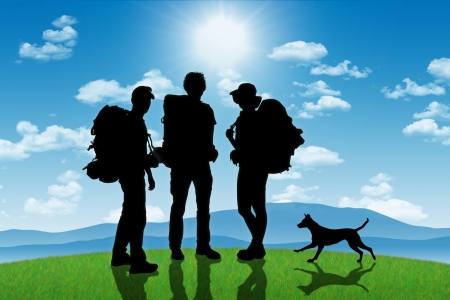 silhouettes of three backpackers, men and a woman, with a dog standing on a top of the hill on mountains landscape background photo