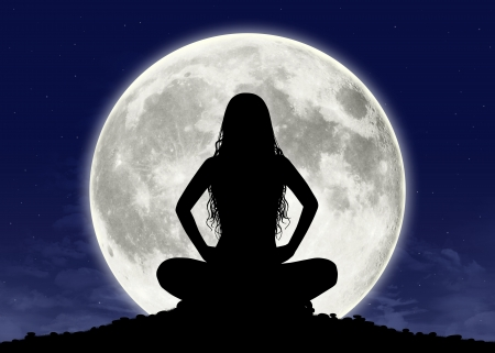 full moon: silhouette of a young beautiful woman with long hair in meditation posture with the full moon on the background