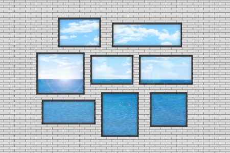 composition of several windows of different size on a white brick wall with a view on a sea landscape photo