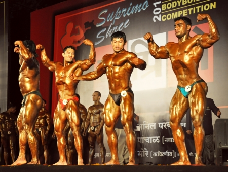 musculation: MUMBAI, INDIA - JANUARY 22, 2011 - several indian bodybuilders with golden bodies making postures on the scene while bodybuilders Editorial