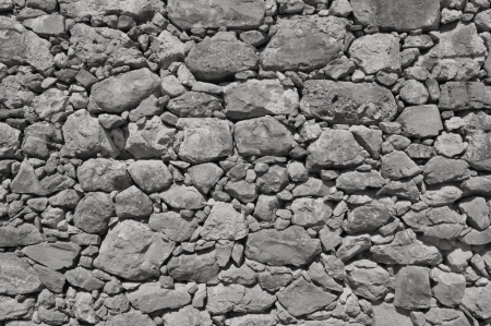 impure: dark grey old wall made of big and little rough stones without cement Stock Photo