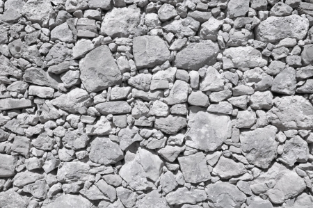 uncouth: grey old wall made of big and little rough stones without cement