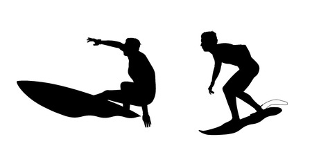 silhouettes of two surfers standing on their boards surfing the waves Stock Photo