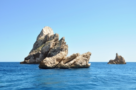 three beautiful rough beige rocks above the blue surface of the sea Stock Photo