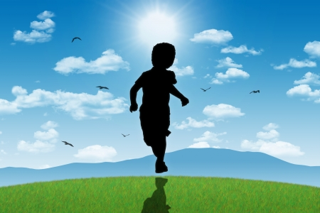 silhouette of a little boy running on a top of a green hill towards the shining sun with mountains landscape on a background Stock Photo