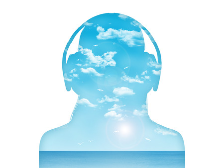 silhouette of a young woman in headphones listening to the music, beautiful blue sea landscape inside her Banque d'images