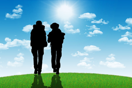 silhouettes of two backpackers, a man and a woman, walking on a top of the hill towards the shining sun Stock Photo