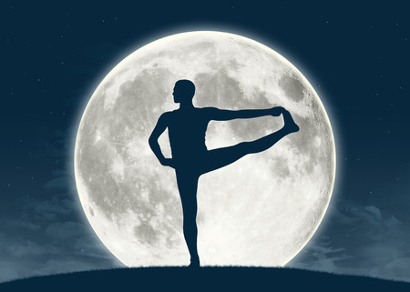 silhouette of a young man practicing yoga with the full moon on the background Banque d'images