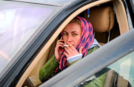 young woman sitting in a car with cigarette photo