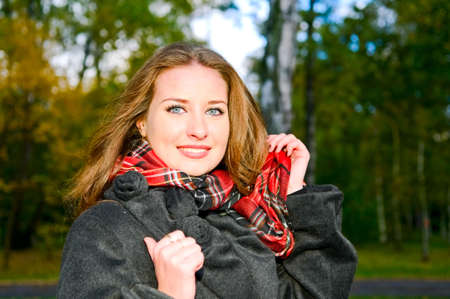 portrait of young smiling woman in autumnal park photo