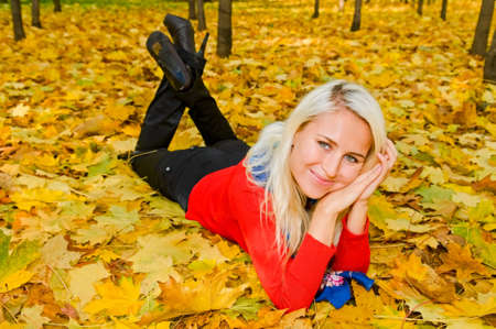 young smiling blonde woman resting on autumn leaves photo