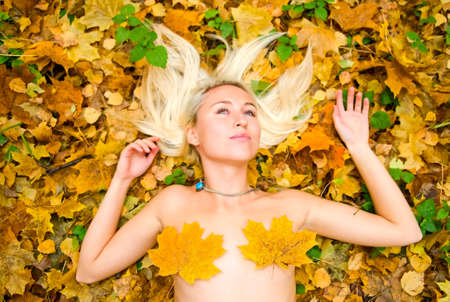 Young blonde woman resting on the grass in autumnal forest Stock Photo - 5712341