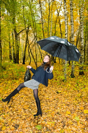Young woman with umbrella in autumn forest photo