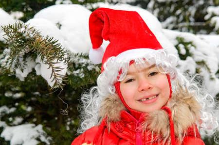 smiling girl in red cap of Santa Claus photo