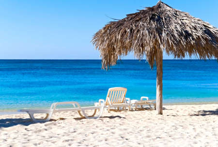 The idyllic beach with deck chairs and umbrella, Ancon, Cuba Stock Photo