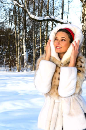 young smiling woman in winter forest photo