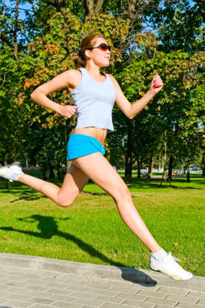 young woman in shorts running in park