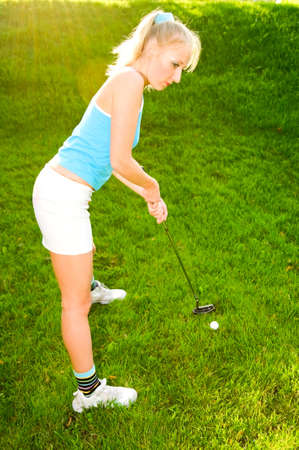 young woman playing golf photo
