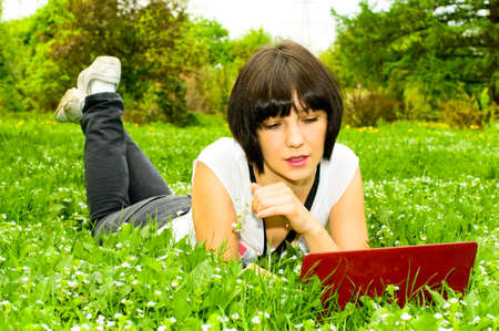 pretty young woman with laptop on the grass photo