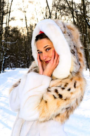 fur tree: portrait of young smiling woman in winter forest  Stock Photo